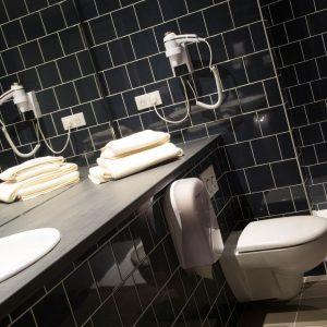 De belles salles de bain aux teintes profondes, équipées de douche à l'italienne.